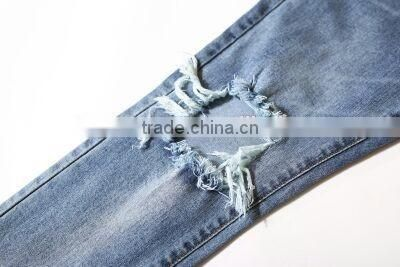 Slightly faded blue jeans with zip down whiskering ripped pants