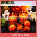 Halloween glass candle with pumpkins on black background