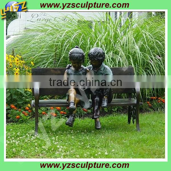 cast bronze boy and girl garden statue reading on the bench