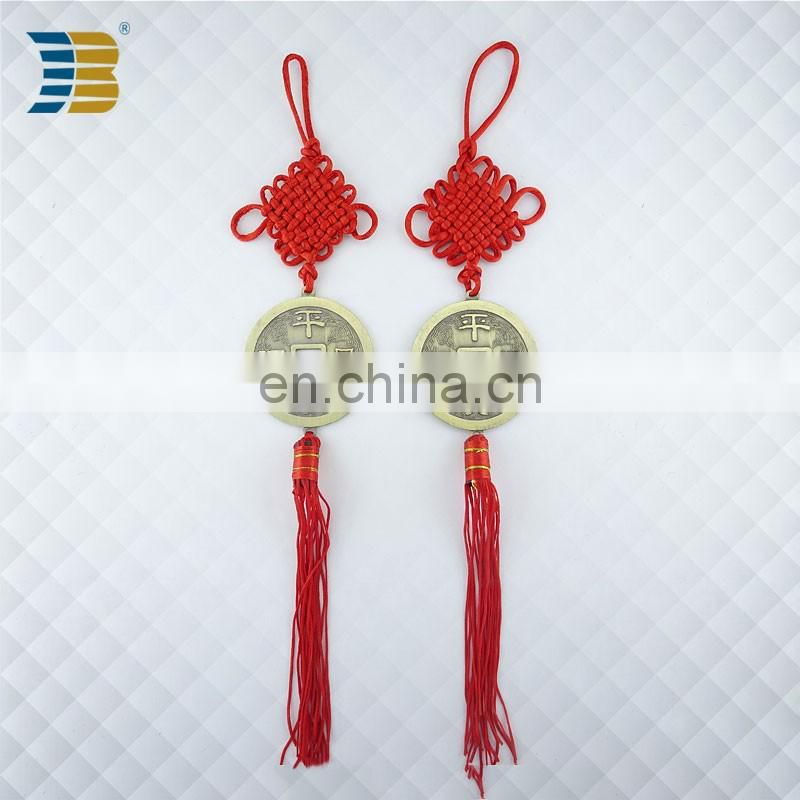 bronze coin with red Chinese knot charm