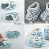 Beautiful handmade knitted woolen baby booties of blue and white colors