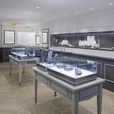 Jewelry retail display fixture in grey wood counter with glass showcase in LED light and curved reception table
