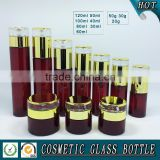 Cylinder RED coloured glass cosmetics bottles and face cream jars
