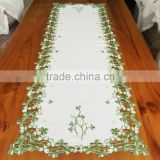 embroidered table runner with shamrock designs on satin material
