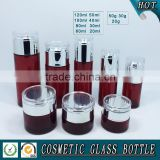 Red coloured cosmetic glass pump bottles and glass cream jars
