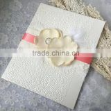 Noble & elegant white embossed wedding invitations with pink ribbons & feather decorations & floral decorations