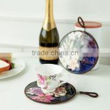 Hot sell round shape ceramic trivet with rope for hanging