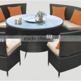 Round based well used patio stacking furniture in top restaurant table and wicker chairs