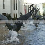 Lots of bronze birds flying in water sculpture