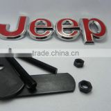 Metal grill emblem with red jeep logo
