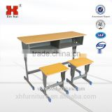 two students with the desks and chairs/school desk and bench