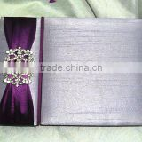 Luxurious & glamorous silver silk gate fold foilo wedding invitations with a small flap & purple ribbon & brooches                                                                         Quality Choice