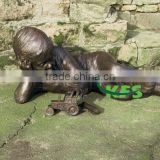 Bronze kid playing tractor statue