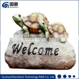 Welcome sign rock with tortoise garden statue