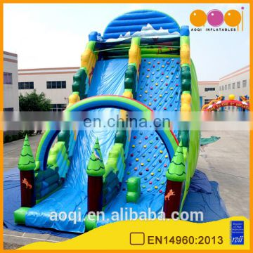 AOQI new style rainbow forest outdoor inflatable high slide with inflatable rock climbing wall for adults
